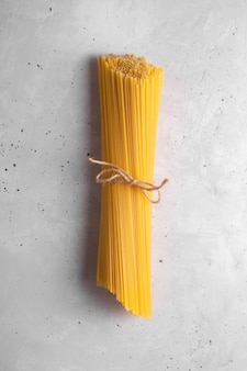 Spaghettis crus. pâtes italiennes sèches préparées à partir de blé dur, fond gris, vue de dessus