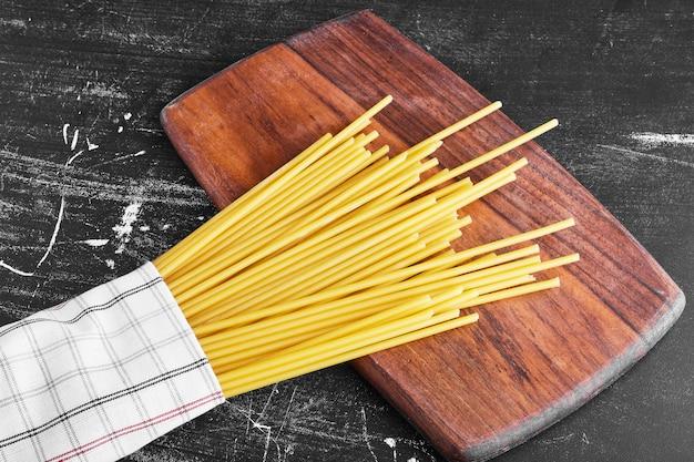 Spaghettis crus sur une planche de bois.