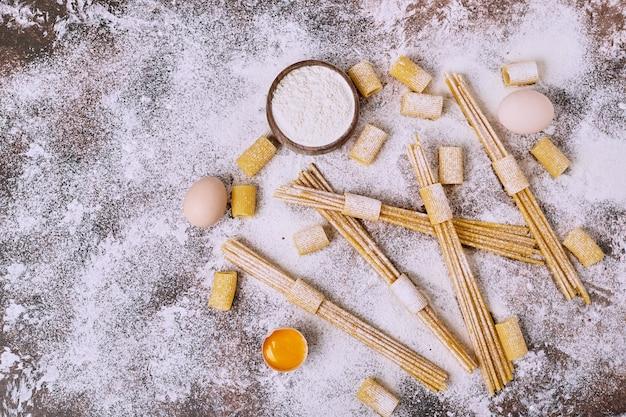 Spaghettis crus sur la surface en bois.