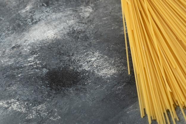 Spaghettis secs crus sur une table en marbre.
