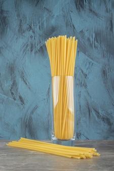 Spaghettis de tube non cuits sur une surface en marbre