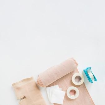 Sparadrap; bandage médical et genouillère sur fond blanc