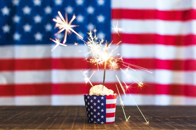 Sparkler brûlant sur petit gâteau sur fond de drapeau usa défocalisé