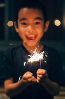 Sparkler sur la main le garçon, dans la fête