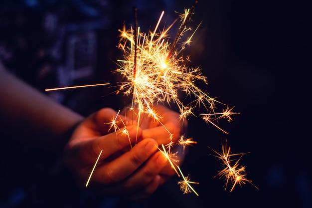 Sparkler de noël, nouvel an dans les mains de la femme.