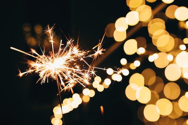 Sparklers sur les lumières de noël floues. ambiance festive.