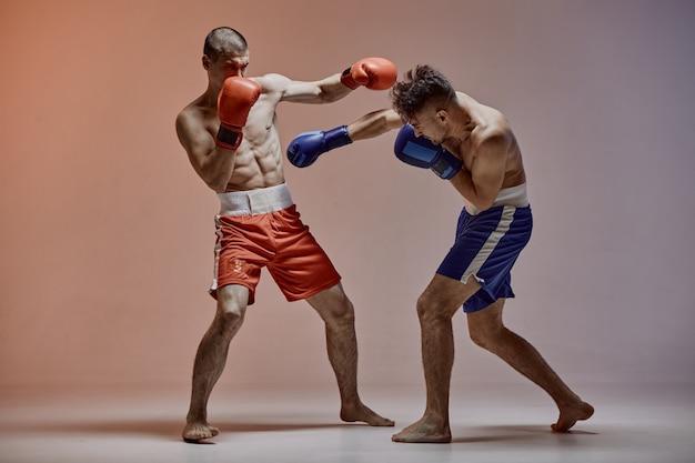 Sparring de deux mâles de combat athlétique dans des gants de boxe pendant la bataille, arts martiaux, combat mixte