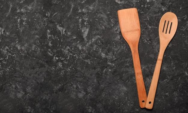 Une spatule en bois et une cuillère pour cuisiner sur une table en béton noir. espace pour le texte. vue de dessus.