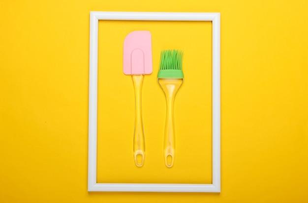 Spatule de cuisine et pinceau sur surface jaune avec cadre blanc