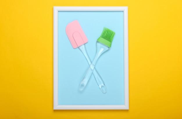 Spatule de cuisine et pinceau sur surface jaune avec cadre photo