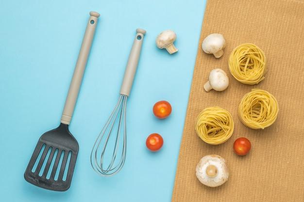 Spatule et fouet de cuisine et ingrédients pour faire des pâtes. ingrédients pour faire des pâtes.