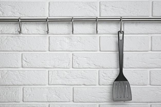 Spatule noire accrochée au rack contre le mur de briques