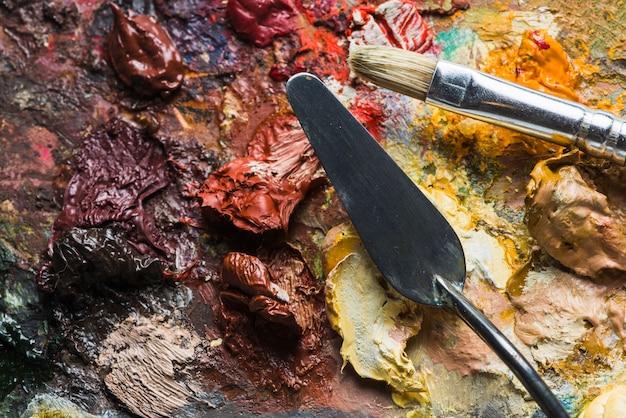 Spatule et pinceau sur des taches de peinture