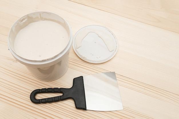 Spatule et un seau de mastic blanc sur des planches en bois