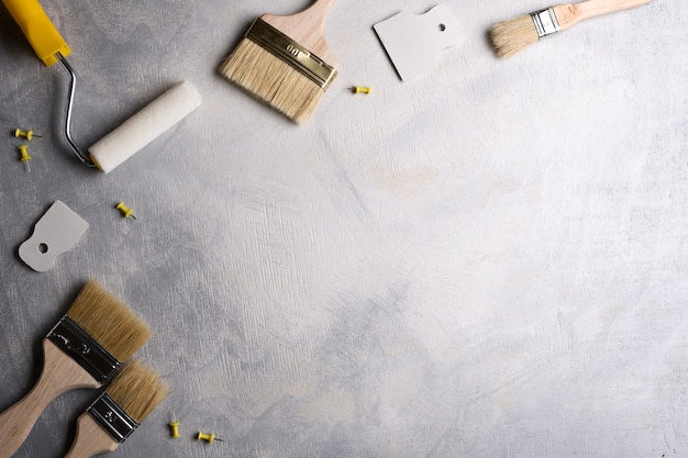 Spatules pour l'application de mastic et pinceaux et rouleaux pour peindre sur un fond de béton gris. vue de dessus