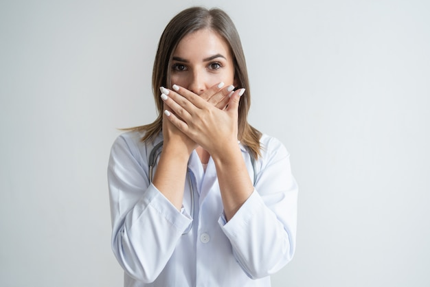 Spécialiste caucasienne choquée en blouse de laboratoire couvrant la bouche