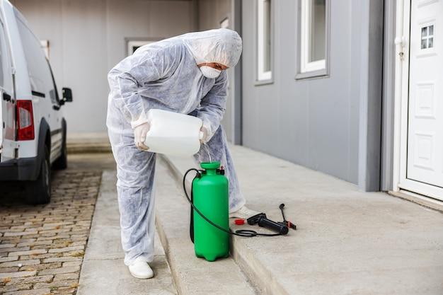 Spécialiste des combinaisons de matières dangereuses se préparant au nettoyage et à la désinfection de l'épidémie de cellules de coronavirus