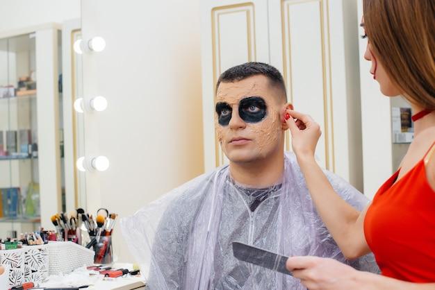 Une spécialiste du maquillage fait un maquillage festif et effrayant pour un homme pour les vacances d'halloween en studio. concept d'halloween heureux.