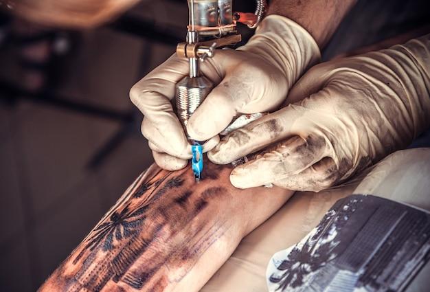 Un spécialiste du tatouage crée un tatouage dans un salon.