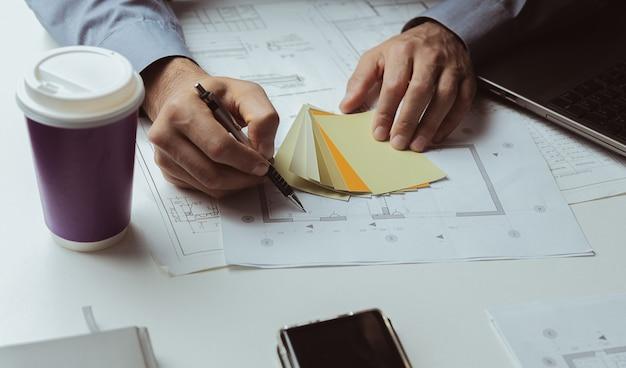 Le spécialiste écrit des marques au crayon sur le plan de la maison et utilise des modèles de couleurs