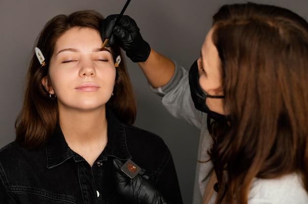Spécialiste féminine faisant un traitement des sourcils pour femme