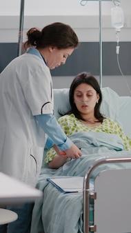 Spécialiste de praticien vérifiant la femme malade hospitalisée se reposant dans le lit