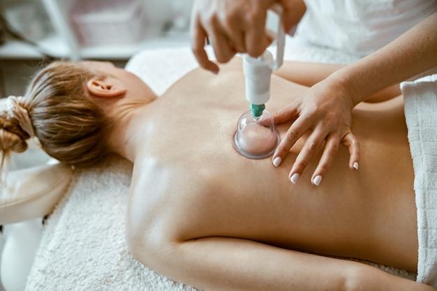 Une spécialiste professionnelle fait une thérapie par ventouses sur le dos d'une belle dame caucasienne