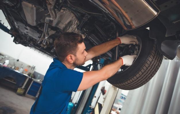 Un spécialiste de la réparation automobile gai, beau et confiant dans la réparation de salopettes et remplace les vieilles pièces par de nouvelles dans une voiture sur un ascenseur en service