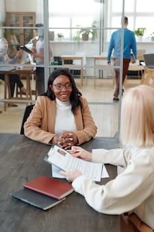 Spécialiste des ressources humaines tenant un curriculum vitae et parlant à une jeune candidate noire tout en la rencontrant au bureau