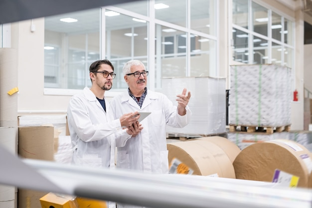 Spécialistes de laboratoire seniors et jeunes en blouse blanche à l'aide de tablette numérique à l'usine tout en parlant de productivité industrielle