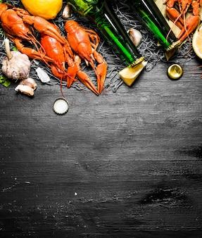 Les spécialités culinaires. écrevisses bouillies avec bière et épices. sur un tableau noir.