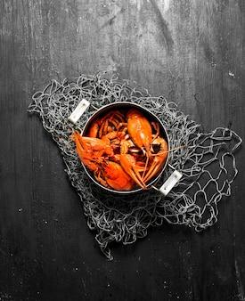 Les spécialités culinaires. écrevisses bouillies fraîches dans le pot sur tableau noir.