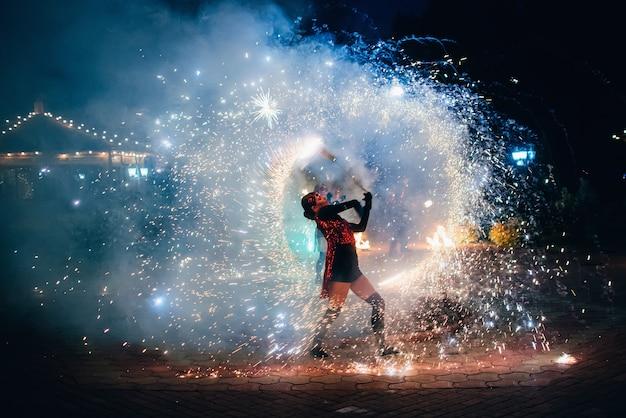 Spectacle de feu. une fille fait tourner des torches étincelantes
