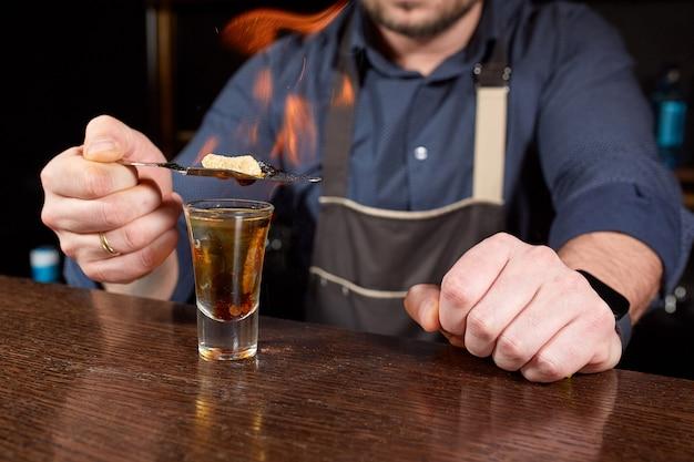 Spectacle fougueux au bar. le barman fait un cocktail alcoolisé chaud et enflamme le bar. le barman prépare un cocktail fougueux. feu sur bar.