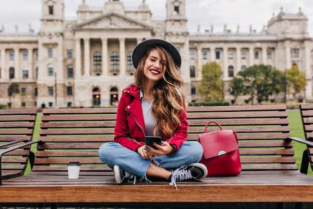 Spectaculaire dame avec une coiffure à la mode assis sur des marches en face de l'ancien bâtiment historique
