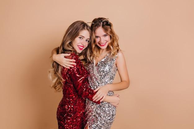 Spectaculaire dame embrassant sa sœur avec tendresse, profitant de la fête de noël