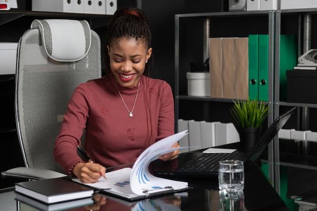 Spectaculaire jeune femme d'affaires noire signe des documents à la table dans le bureau