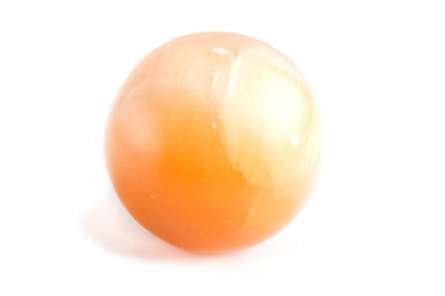 Sphère d'onyx orange isolée sur une surface blanche