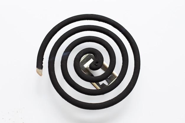 Spirale anti-moustique spirale noire sur fond blanc.