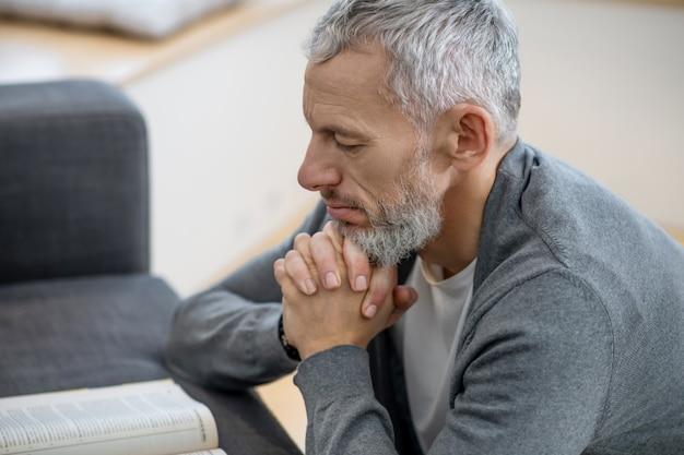 Spiritualité. un homme aux cheveux gris assis les yeux fermés et disant les payeurs