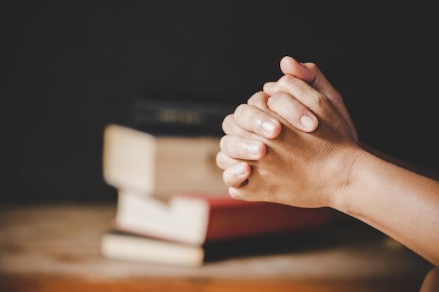 Spiritualité et religion, mains jointes en prière sur une sainte bible dans le concept de l'église pour la foi.