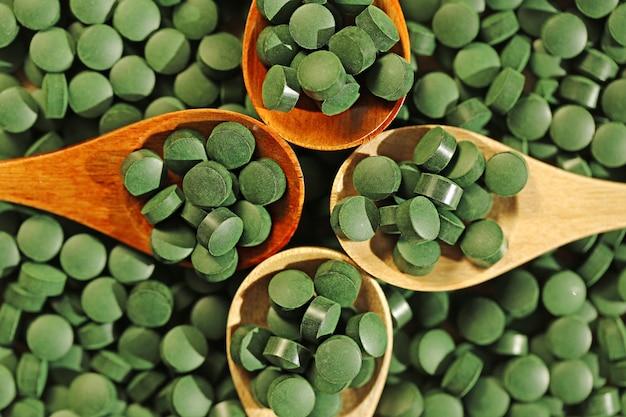 Spiruline. pilules de spiruline dans quatre cuillères en bois. superaliments, algues