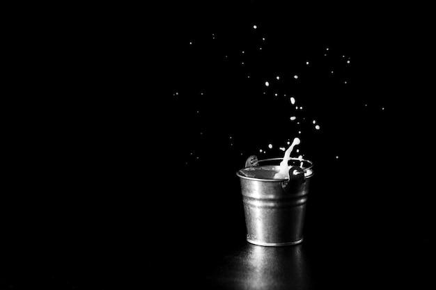 Splash dans un seau en métal avec du lait sur fond noir