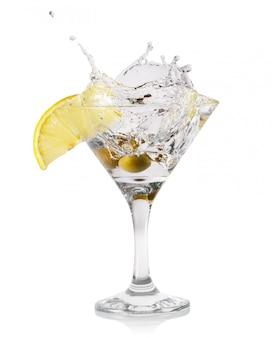 Splash martini avec des gouttes et des olives dans un verre transparent
