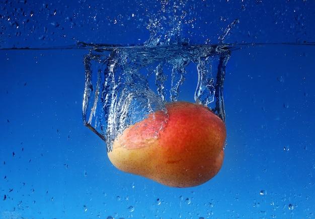 Splash avec poire sur un mur bleu