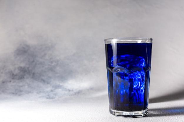 Splash rafraîchissant cocktail bleu d'été rafraîchissant avec des glaçons sur fond avec place pour le texte