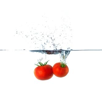 Splash de tomates rouges fraîches dans l'eau