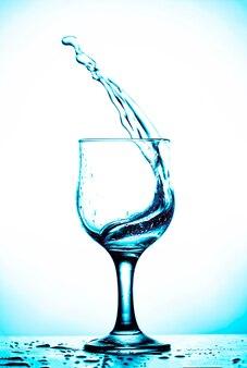Splash de vin dans un verre avec fond d'ombre bleu ciel