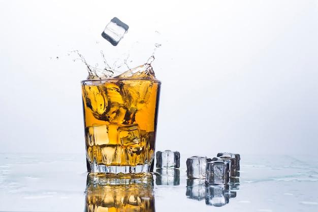 Splash de whisky de glaçons. concept de boissons alcoolisées avec de la glace, du whisky ou du brandy, du jus de pomme et des boissons rafraîchissantes. .