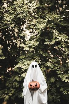 Spooky tenant la citrouille près de la brousse